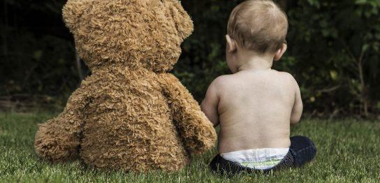 クマのぬいぐるみと一緒の赤ちゃん